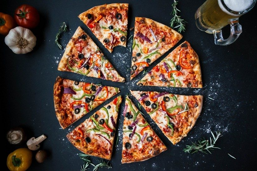 A delicious italian pizza surrounded by fresh ingredients, garlic, tomatoes and peppers