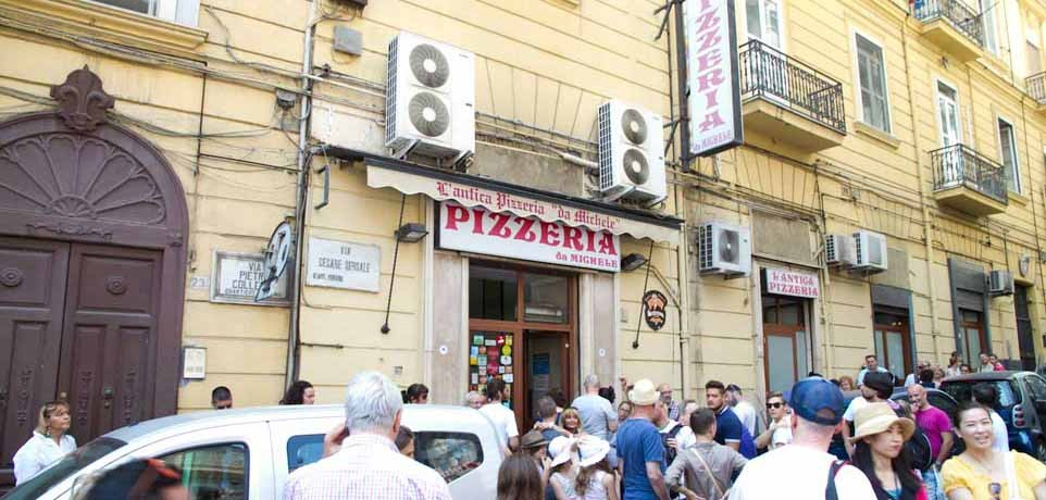 The shop facade of L'Antica Pizzaria Da Michelle on a busy, bustling street