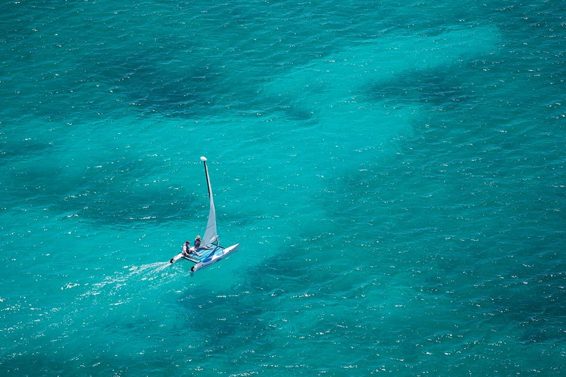 An aerial view of a catamaran shooting through what i can only describe as the most astonishingly clear, blue ocean. Two very happy looking tourists sit, enjoying the moment