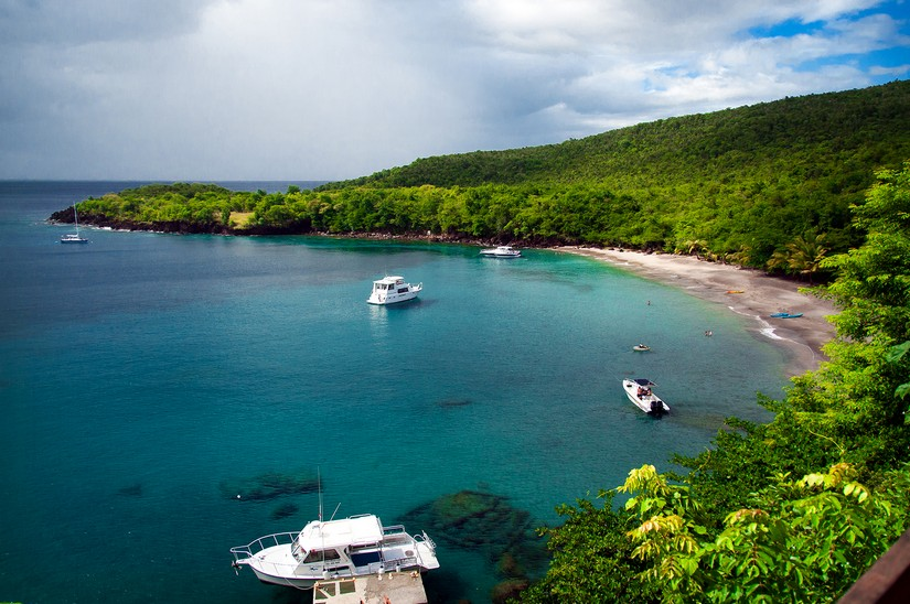 Anse Cochon is a quiet little beach encompassed by a soothing green shawl of lush tropical trees. In the bay a number of white boats bob gently on the water