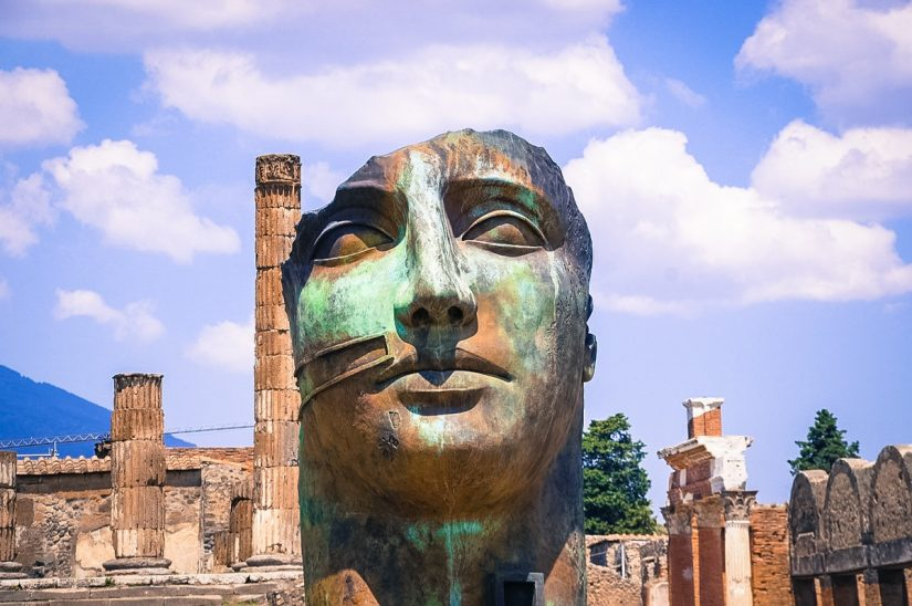 Sculpture of some unknown mythological Roman figure at Pompeii. Created by Igor Mitoraj it is one of 30 pieces located throughout the site. It's looks like tarnished brass and is missing the top of its head