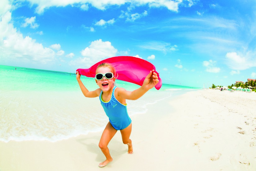 A young girl runs along the powdery white sand of Grace Bay beach with a pink shawl held as if to generate lift and eventually flight. One of the best things to do in Turks and Caicos with kids is to train them to fly!