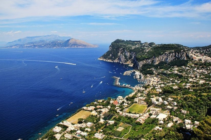 Aerial View of Capri. From they sky. Lots of little white buildings huddled along a coast of deeply blue water dotted with white yachts and boats cruising affably from place to place.