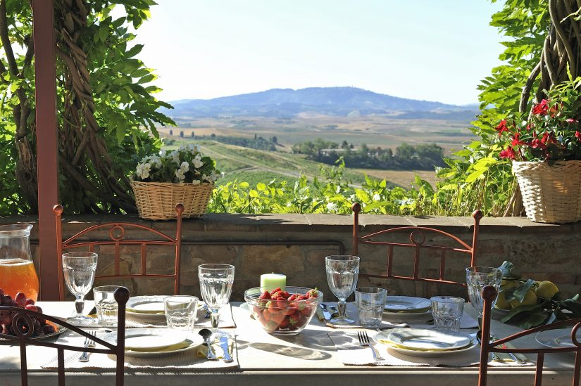 A sunlit table laden with wholesome lunchytype foods on a balcony over-looking an exquisite tuscan landscape