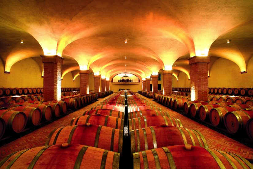 A warmly lit vaulted wine-cellar full of barrels of delicious vintage