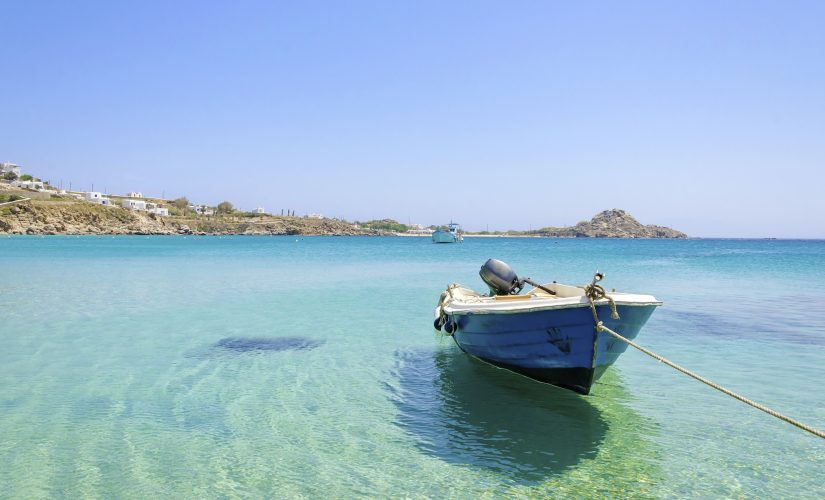 A small wooden boat bobs enthusiastically on the water of Platys Gialos. What to do in Mykonos is to Visit Platys Gialos!