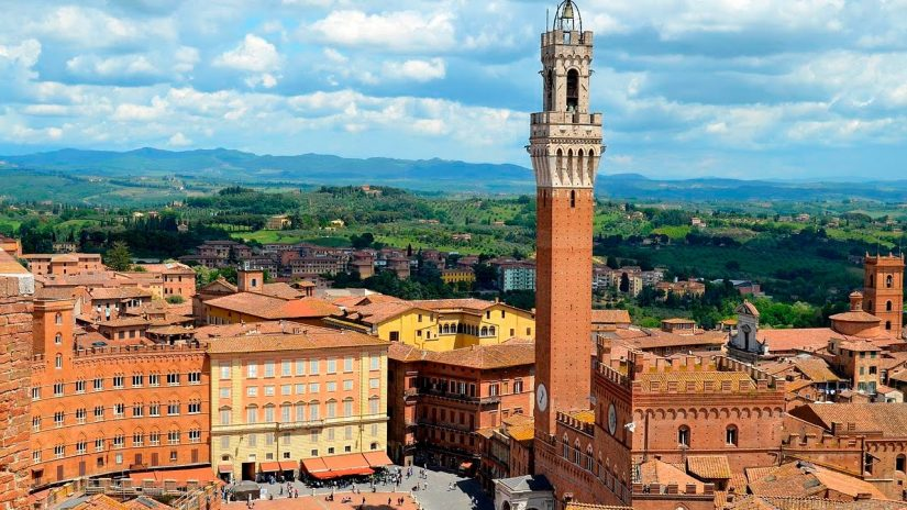 The beautiful red sandstone city centre and tower of Siena in Tuscany