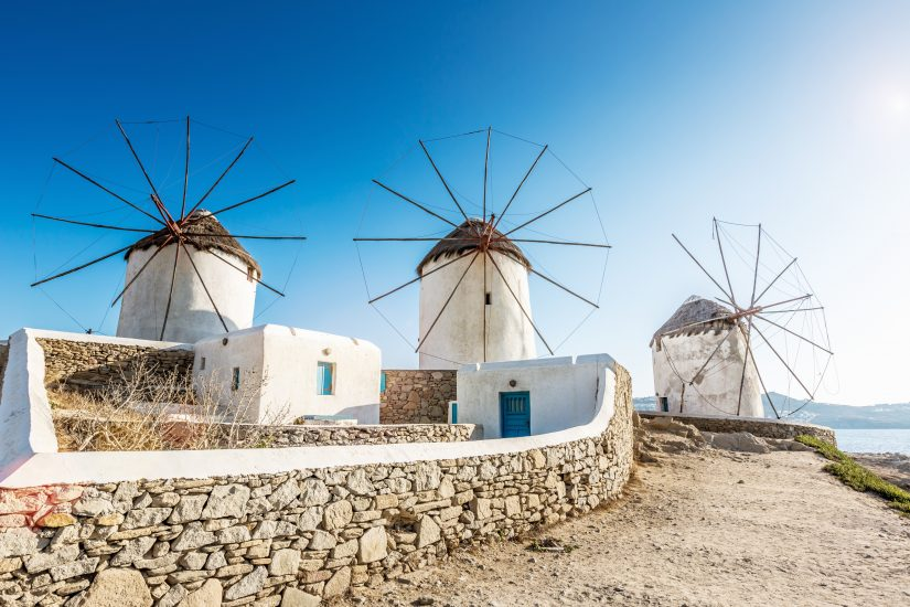 Three aging, white-washed windmills stand in a line with a terrifyingly beautiful blue sky in the background.