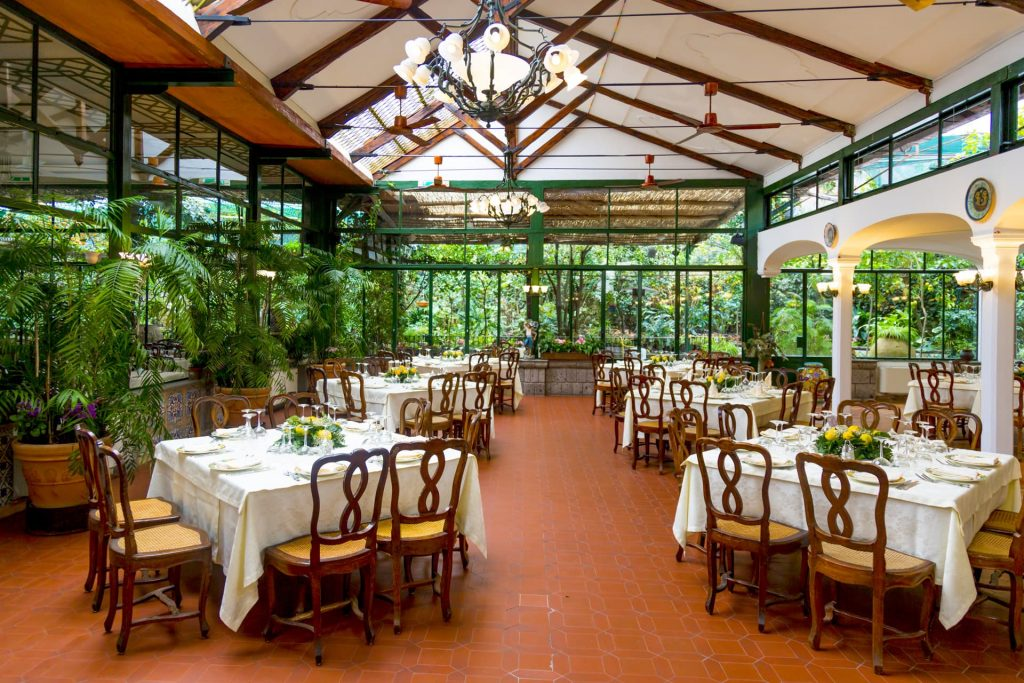 O'Parrucchiano Restaurant in Sorrent is sset in a high ceilinged atrium surrounded by beautiful gardens. The floor is covered with orange terracotta tiles and the colour scheme is green and white.