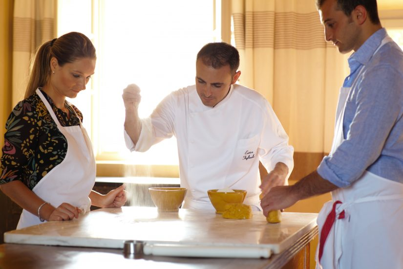 A chef at a Tuscany cooking school demonstrates to guests