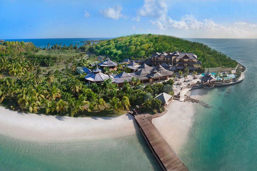 Aerial shot of calivigny island Pagoda style roofs emerges surreptitiously from the thick canopy of palm trees that shade the rental villa from the hot Caribbean sun