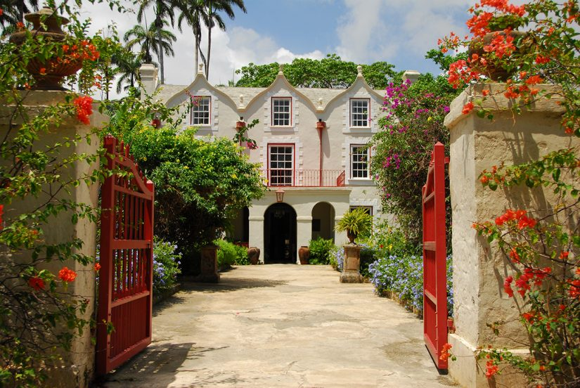 St Nicolas Abbey - A majestic Barbados Attraction sits peacefully among the vibrant red and orange flowers and landscaped gardens.