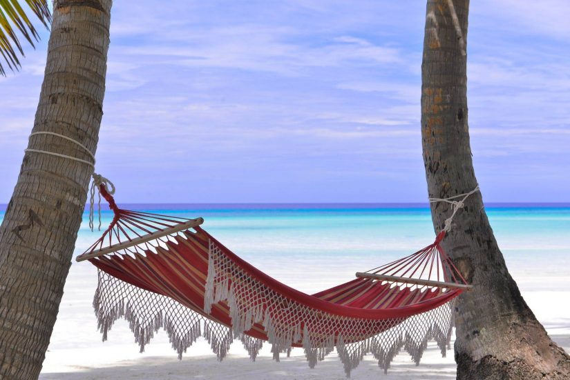 Hammock strung between two palm trees on a beach in the Caribbean