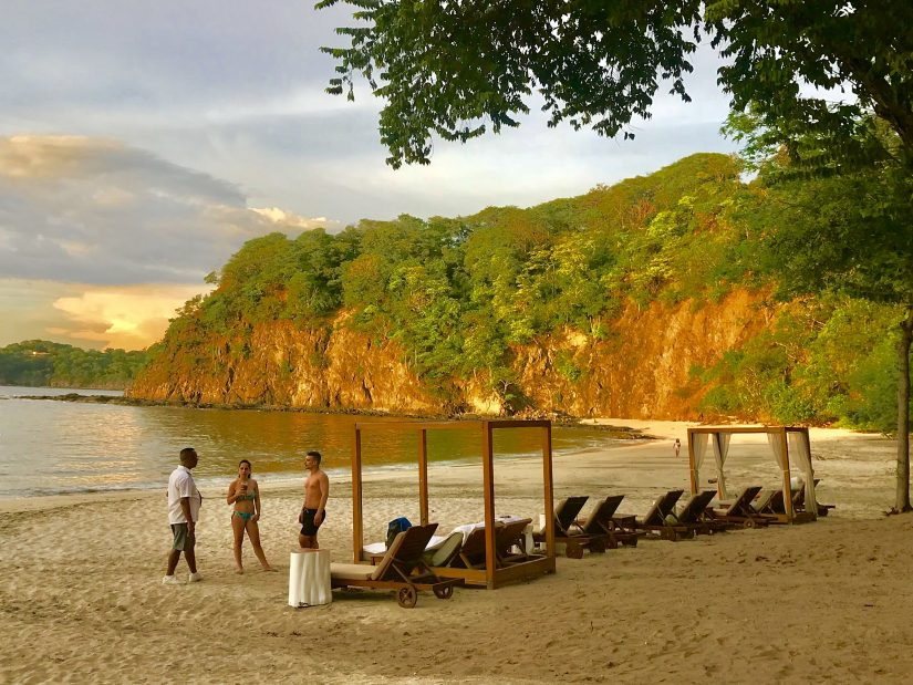A picturesque beach in costa rica with sun loungers