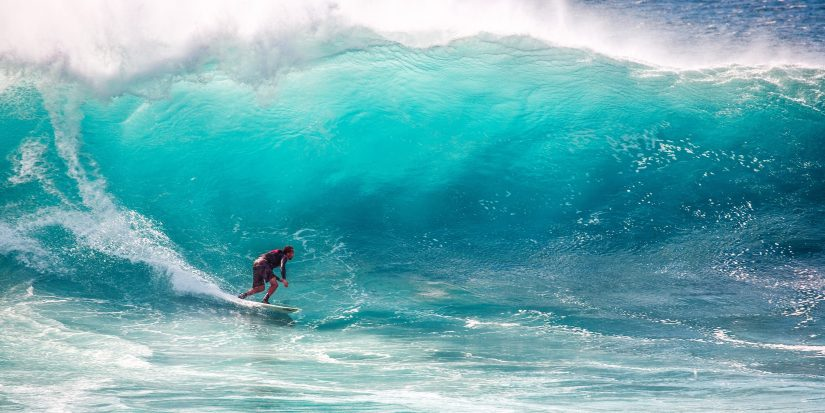 A surfer braves an epic crashing wave