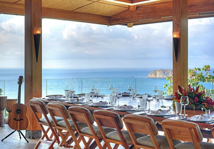 The dining area at Villa Panorama.  Lots of chairs and a big table with the Pacific Ocean in the background