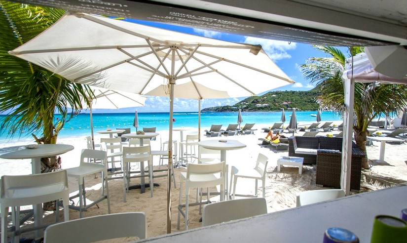 Pearl Beach Restaurant with its sun loungers high tables, high stools, and parasols looking out over the beach