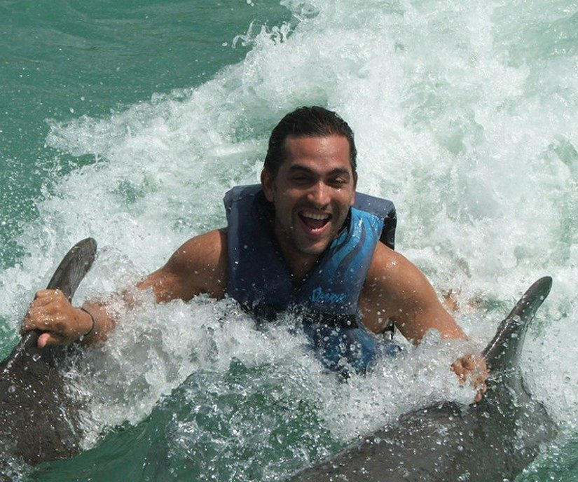 Man swimming with dolphins at half moon resort