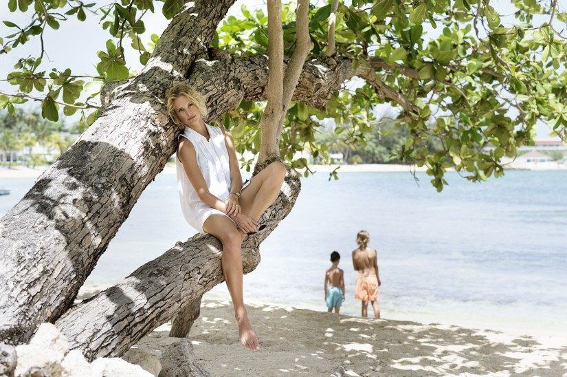 woman sitting on tree at a jamaica resort