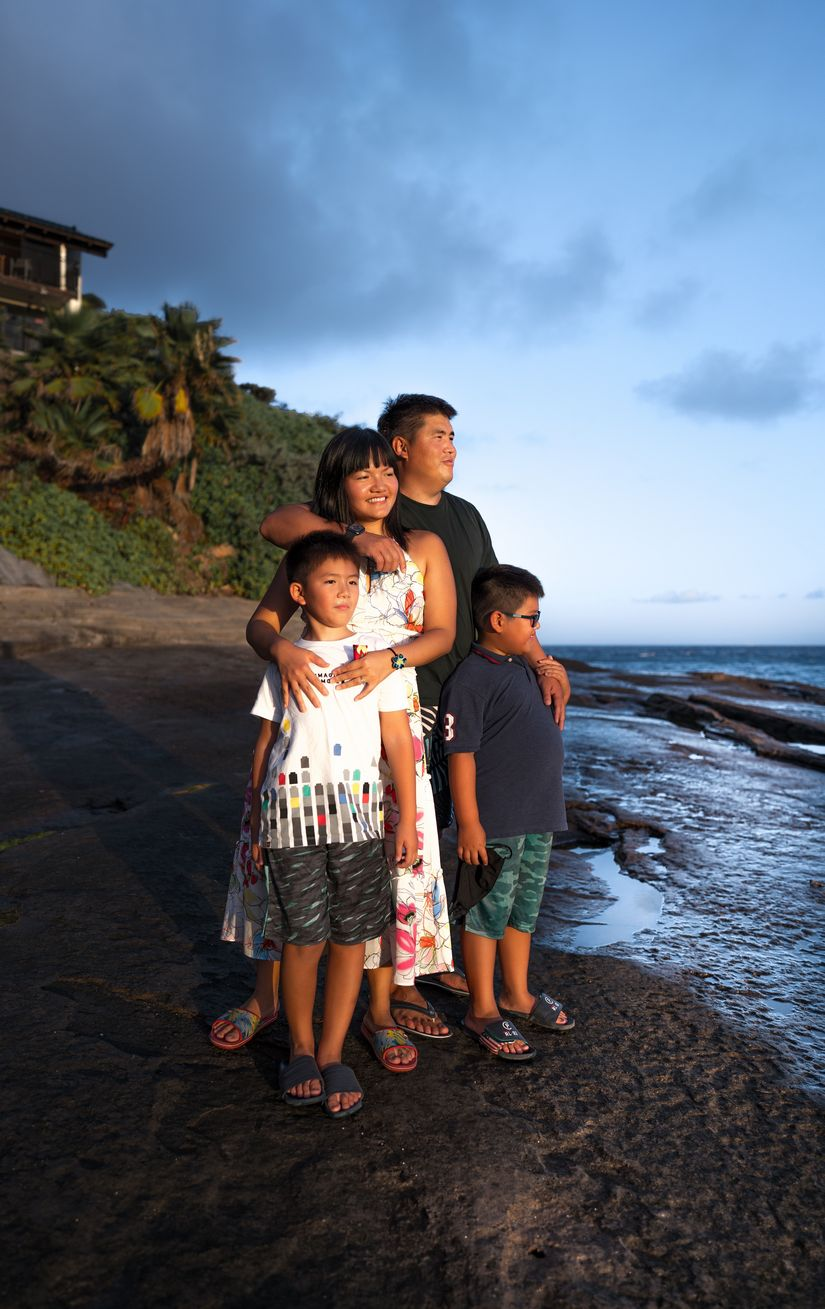Family stands on a beach looking towards the sea in the Caribbean