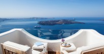 A luxury passenger cruiser makes its way to port in the Aegean Sea as seen from the stylish, clean-cut white balcony at Villa Gaia.