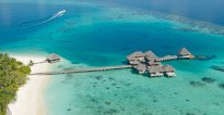 A collection of Over Water Villas linked by causeway to a lush tropical atoll in the Maldives