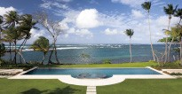 Elevated view of palm trees, sea, and the pool area at Su Casa, Dorado Beach, Puert Rico.