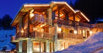 Les Anges luxury chalet illuminated at night by the soft glow of lights and set in a romantic blanket of Alpine snow.