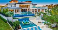Villa Babette in Miami with blue skies and a wide set of steps into the pool.