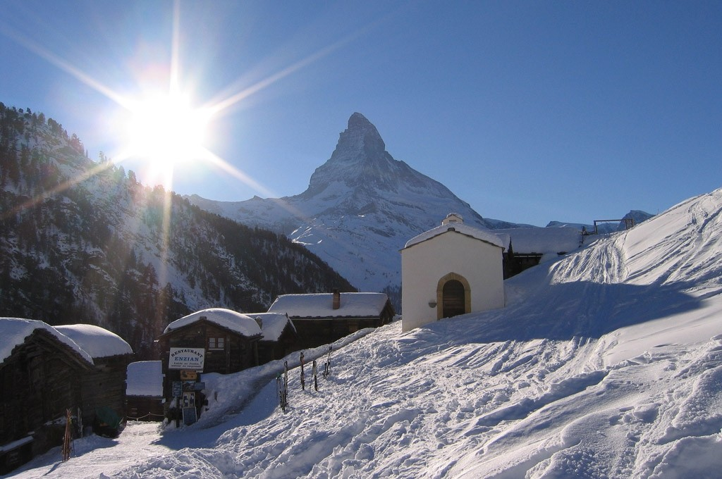 bright morning sun shines over the mountain peaks on chalets in Zermatt
