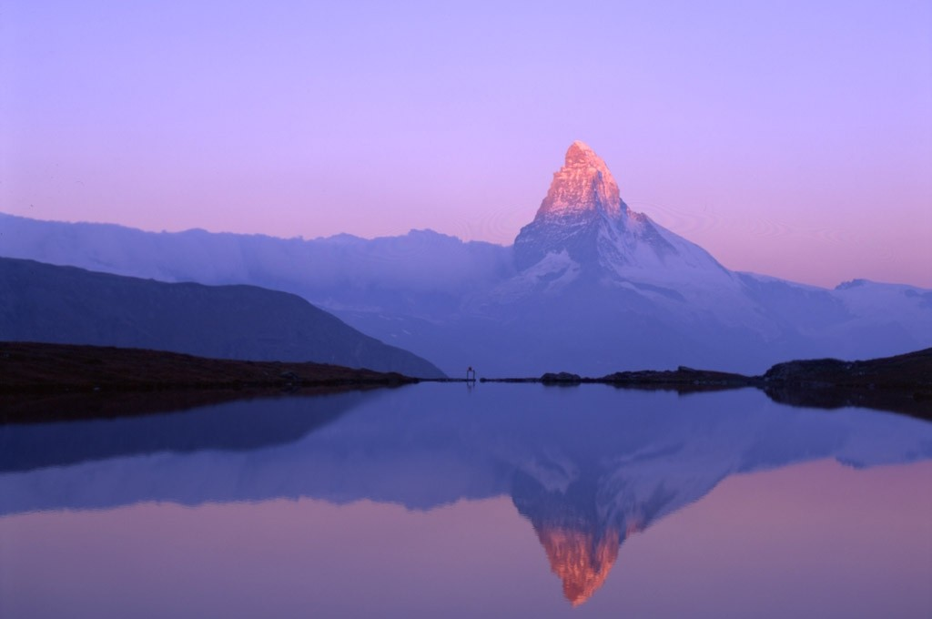 The Matterhorn bathed in the first rays of the morning sun as seen across a crystal clear mountain lake