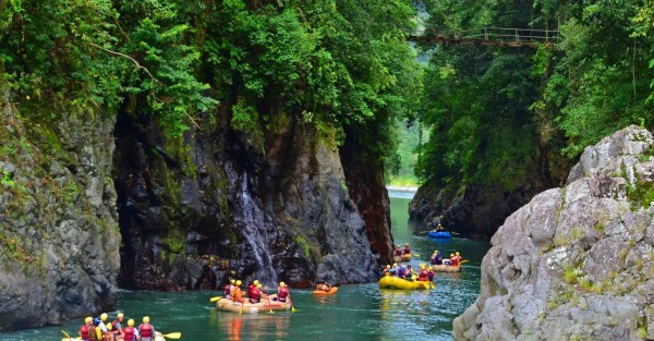 Inflatable boats meander down a river in Costa Rica taking their passengers on a river adventure