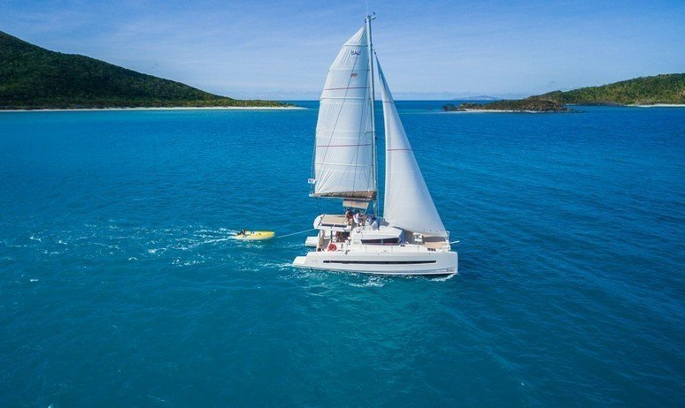A luxury yacht charter catamaran cruises gracefully through the Caribbean sea
