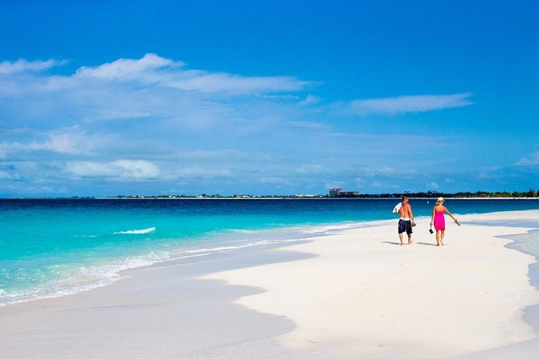 Big white sandy beach at grace bay with couple walking along it.