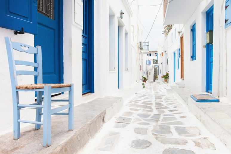 Bright white narrow street with vividly blue doors set into walls on a thin pavement