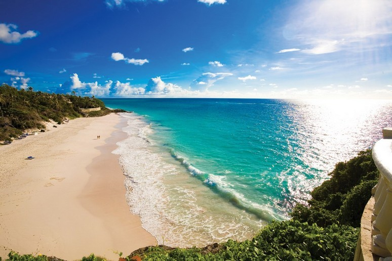 The beach at Crane resort arcs golden powdery sand along the edge of the beautiful azure ocean
