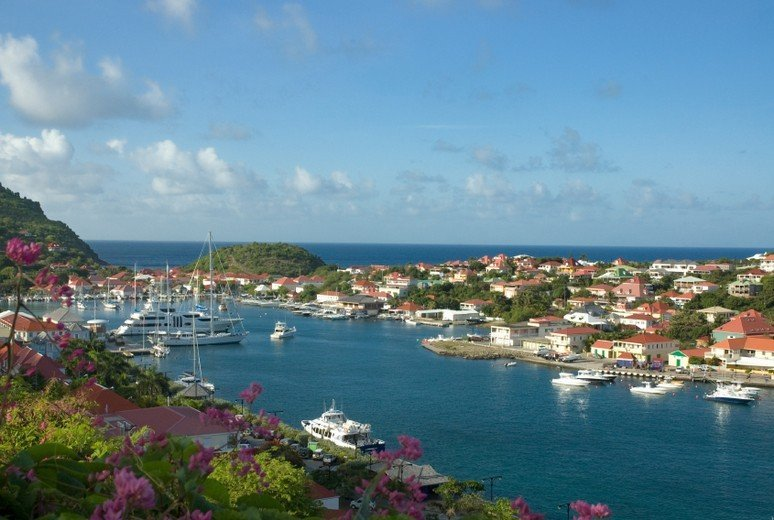 View of the harbour at Gustavia.  Great big yachts loom palely from the water.  The harbour is flanked by a profusion of clean white buildings roofed with with clay-red tiles