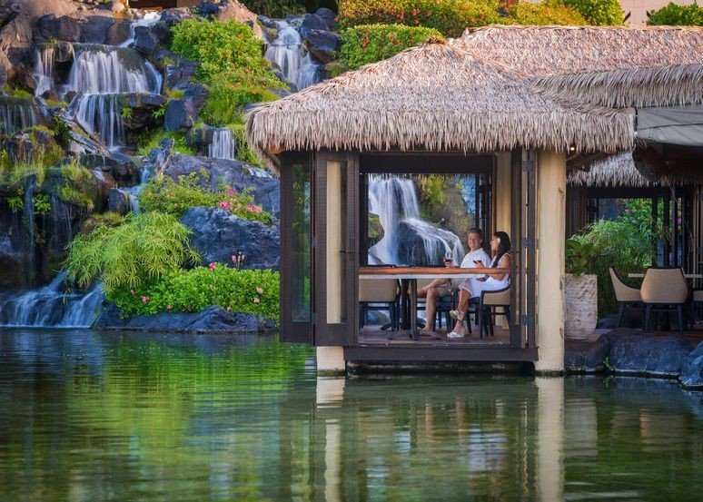 A couple sit by the waterside at the Tidepools restaurant in Kauai