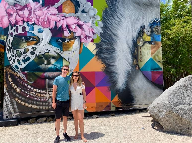 A young couple pose in front of a huge mural in Wynwood Walls, Miami