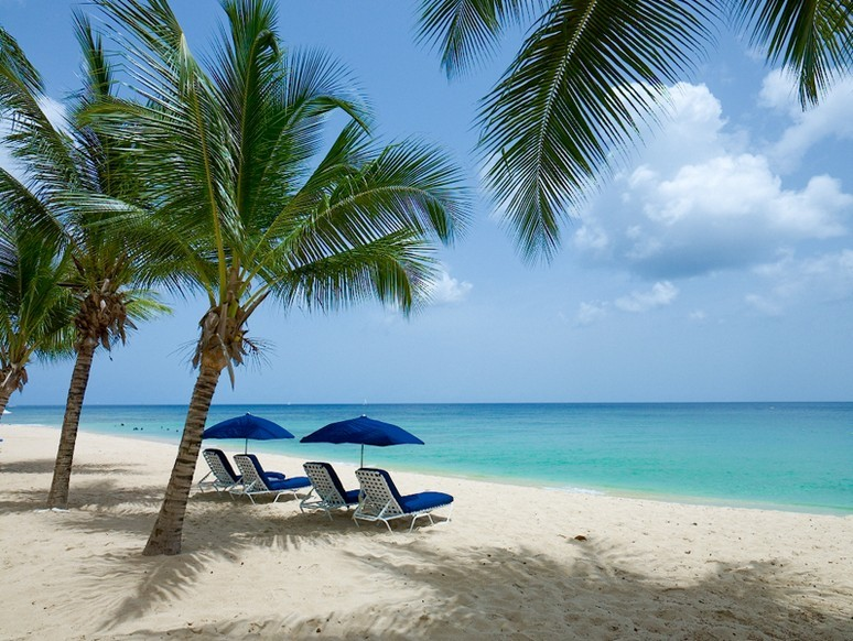 A pair of sun loungers look at the Caribbean Sea from under the cover of fa cooling parasol