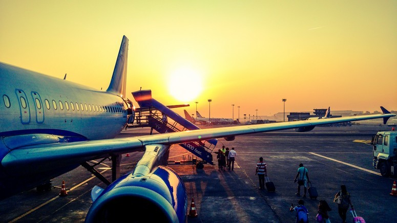 Passengers boarding a plane at sunset