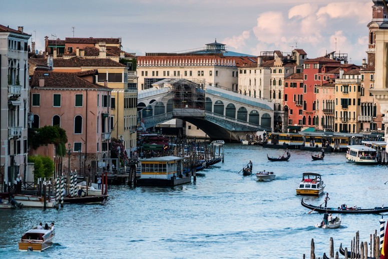 The Rialto Bridge in Venice spans a river busy with ferries and gondolas