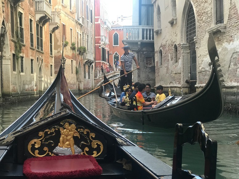View from a Gondola moving through a canal in Venice
