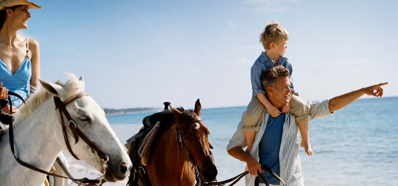 A family rides horses in the Punta Cana Luxury Resort