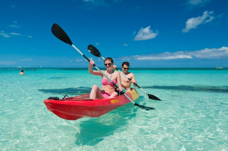 A man and a woman kayak in shallow water off COMO Parrot Cay in Turks and Caicos