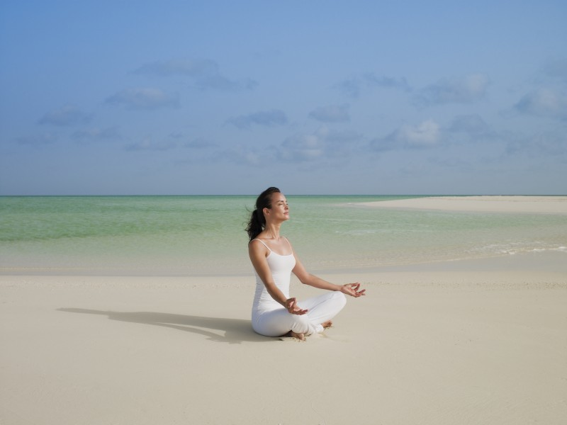 A girl in white meditates on the golden sandy beach at COMO Parrot Cay
