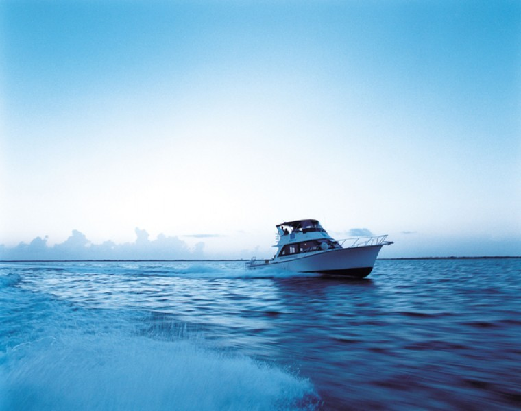 A white fishing yacht plys the waves of the Caribbean Sea