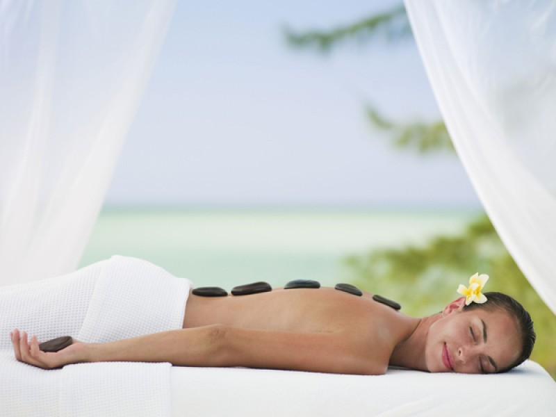A lady lying down getting warm stone therapy at COMO Parrot Cay in Turks and caicos
