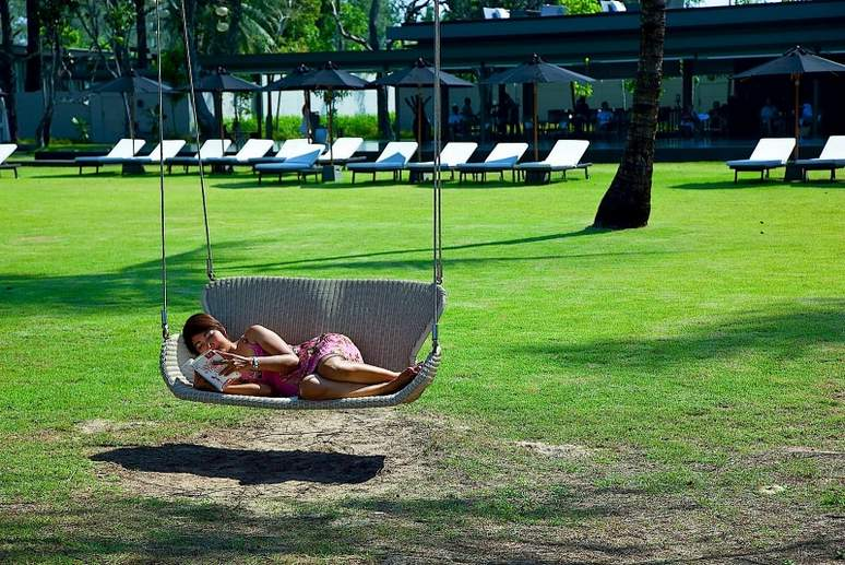 A guest reading a book in a swing chair at SALA Phuket