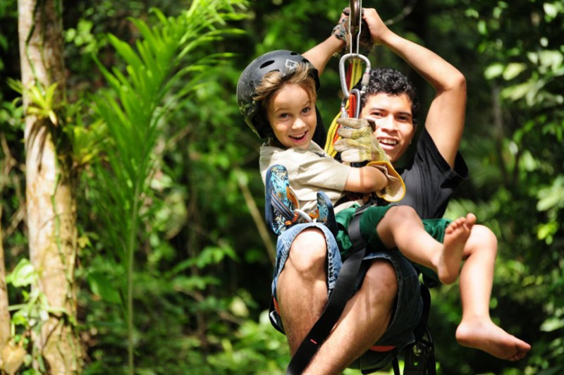 Two children happily zip-lining through lush tropical undergrowth at St Barts Adventure